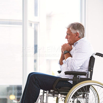 Buy stock photo Shot of a focused mature man sitting in a wheelchair while contemplating inside a clinic