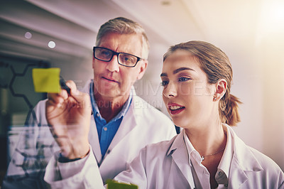 Buy stock photo Shot of two focused scientists working together solving equations on a glass wall in a laboratory