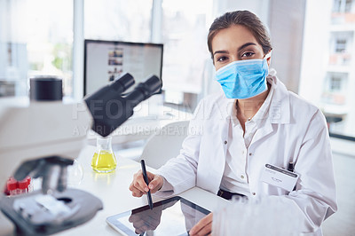 Buy stock photo Portrait of a confident young female scientist wearing a surgical mask and working on a digital tablet while looking at the camera in a laboratory