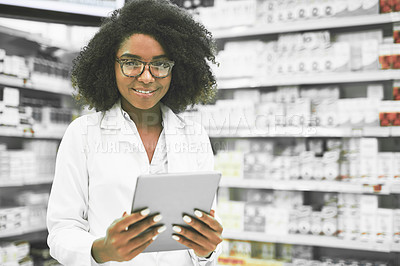 Buy stock photo Portrait of a cheerful young female pharmacist standing with a digital tablet while looking at the camera in a pharmacy