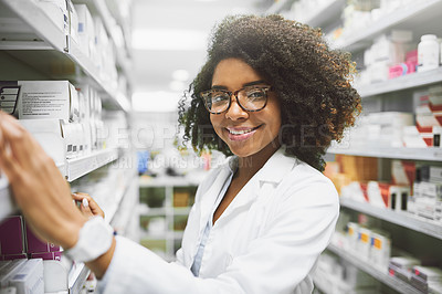 Buy stock photo Portrait of a cheerful young female pharmacist packing medication on shelves inside of a pharmacy while looking at the camera
