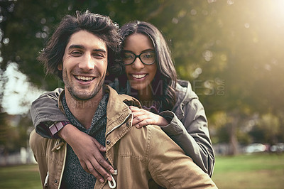 Buy stock photo Portrait of a cheerful young couple having a piggyback ride while looking at the camera outside in a park