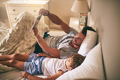 Buy stock photo Shot of a father and his little son using a digital tablet while lying in bed at home