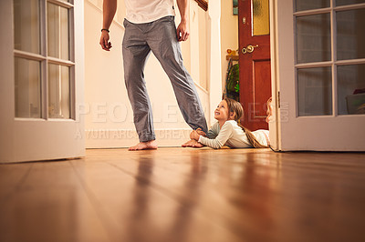 Buy stock photo Shot of a cheerful little girl grabbing hold of her dad's leg and not letting go while lying on the ground at home