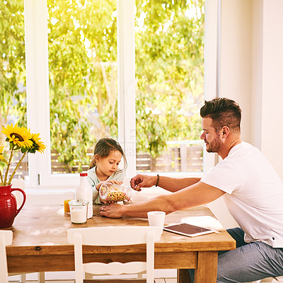 Buy stock photo Shot of a cheerful father and daughter having breakfast together while being seated around a table at home