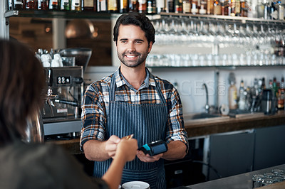 Buy stock photo Shot of a cheerful young barman receiving a card as payment from a customer inside of a restaurant