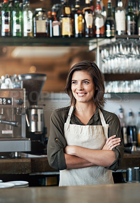Buy stock photo Shot of a cheerful female bartender standing behind the bar counter with her arms folded