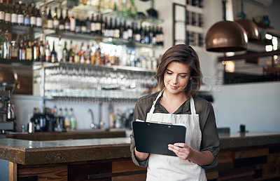 Buy stock photo Shot of a cheerful young female bartender making notes in a book while standing next to a bar counter