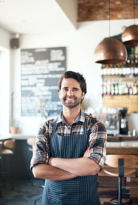 Buy stock photo Portrait of a cheerful young male bartender standing with arms folded inside of a restaurant
