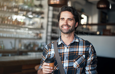 Buy stock photo Shot of a cheerful young man standing with a coffee in his hand inside of a restaurant