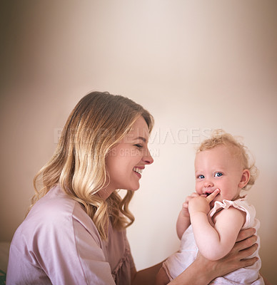 Buy stock photo Shot of a young woman bonding with her baby girl at home