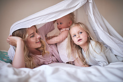 Buy stock photo Shot of an adorable family of three playing under a sheet on the bed at home