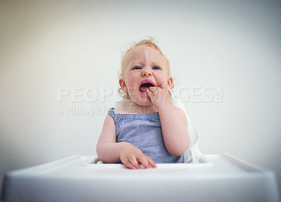 Buy stock photo Shot of an adorable baby girl sitting in her high chair at home