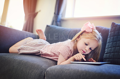Buy stock photo Shot of an adorable little girl using a digital tablet on the sofa at home