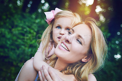 Buy stock photo Shot of an adorable little girl bonding with her mother during a day outdoors