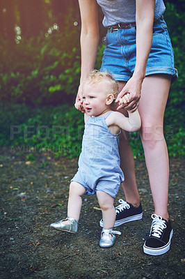 Buy stock photo Shot of an adorable baby girl learning to walk with help from her mother outdoors