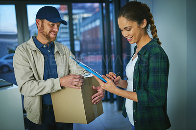 Buy stock photo Shot of a young woman signing for a package from a delivery man