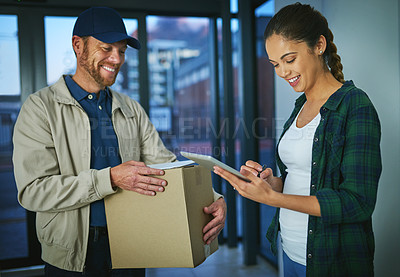 Buy stock photo Shot of a young woman using a digital tablet to sign for a package from a delivery man