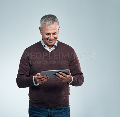 Buy stock photo Studio shot of a mature man using a digital tablet against a gray background