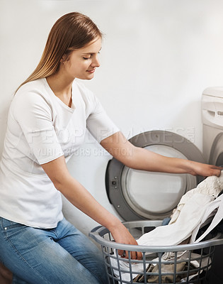 Buy stock photo Shot of an attractive young woman doing laundry at home