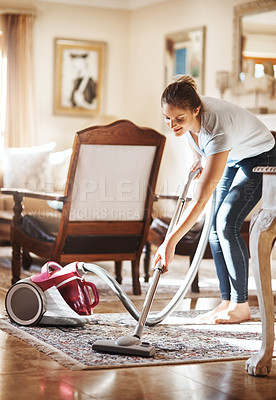 Buy stock photo Shot of a young woman vacuuming her living room