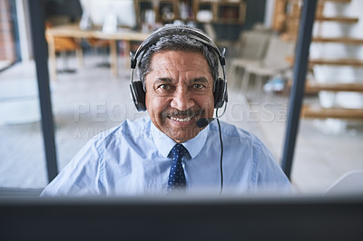 Buy stock photo Portrait of a cheerful businessman talking to a customer using a headset while looking at the camera