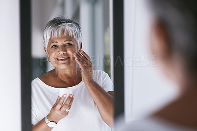 Buy stock photo Shot of a cheerful mature woman applying skin cream on her face while looking into a mirror at home