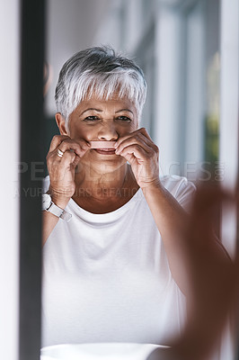 Buy stock photo Portrait of a cheerful mature woman waxing her moustache while looking into a mirror at home