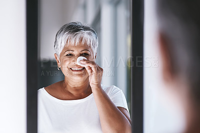 Buy stock photo Shot of a cheerful mature woman applying makeup remover on her face while looking in a mirror at home