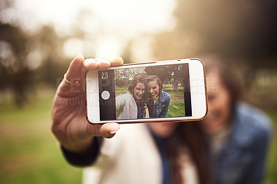 Buy stock photo Shot of two cheerful young friends taking a self portrait together outside in a park
