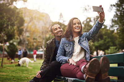 Buy stock photo Shot of a cheerful young couple sitting down on a bench while taking self portraits together outside in a park