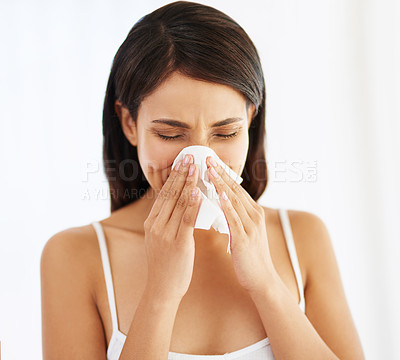 Buy stock photo Shot of a young woman blowing her nose at home