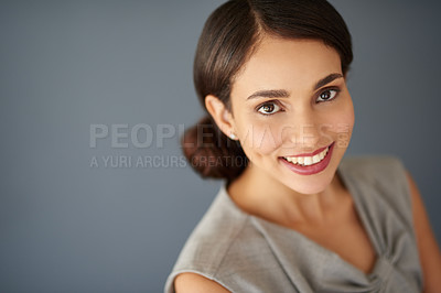 Buy stock photo High angle studio portrait of an attractive young businesswoman posing against a gray background