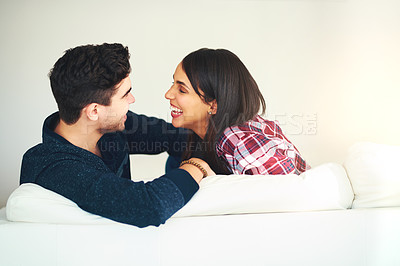 Buy stock photo Cropped shot of an affectionate young couple relaxing on the sofa at home