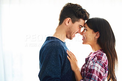 Buy stock photo Cropped shot of an affectionate young couple standing face to face in their home