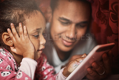 Buy stock photo Shot of a father and his daughter using a digital tablet together at bedtime