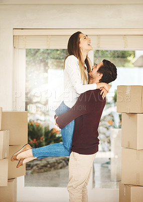 Buy stock photo Cropped shot of an affectionate young couple embracing while moving into a new home