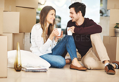 Buy stock photo Shot of an affectionate young couple taking a coffee break while moving into a new home