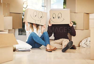 Buy stock photo Shot of a young couple day wearing boxes with smiley faces drawn on them on moving day