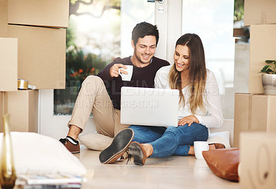 Buy stock photo Full length shot of a young couple using a laptop while moving into a new home