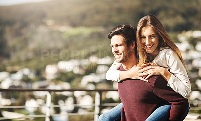 Buy stock photo Cropped shot of a handsome man carrying his girlfriend on his back on their balcony