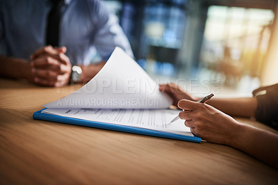 Buy stock photo Cropped shot of a man and woman completing paperwork together at a desk
