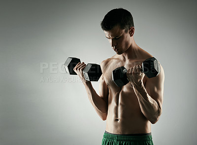 Buy stock photo Studio shot of a shirtless young male athlete working out with dumbbells against a grey background