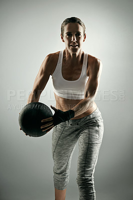 Buy stock photo Studio portrait of an athletic young woman working out with a medicine ball against a grey background