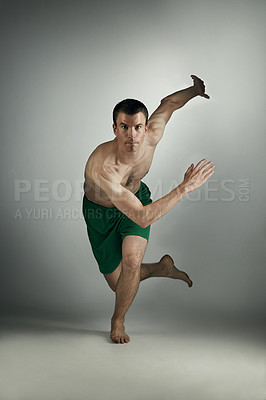 Buy stock photo Studio portrait of a shirtless young male athlete running against a grey background