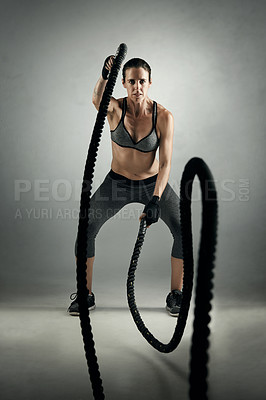 Buy stock photo Studio portrait of an athletic young sportswoman working out with battle ropes against a grey background