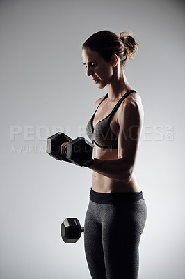 Buy stock photo Studio shot of an athletic young sportswoman working out with dumbbells against a grey background