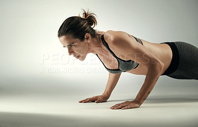 Buy stock photo Studio shot of an athletic young sportswoman working out against a grey background