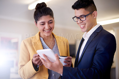 Buy stock photo Shot of two young businesspeople using a digital tablet in an office