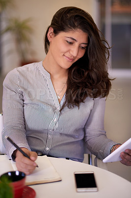 Buy stock photo Shot of a young businesswoman writing notes while using a digital tablet in an office